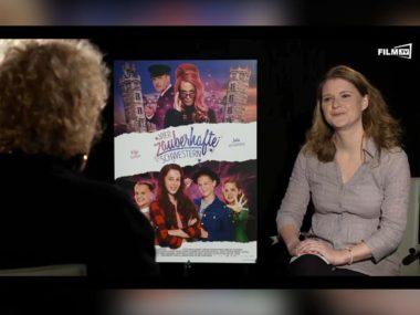 Interviewerin Jessica Neumayer auf der rechten Seite vor dem Kinoplakat zu Vier zauberhafte Schwestern. Auf der linken Seite Katja Riemann von hinten.