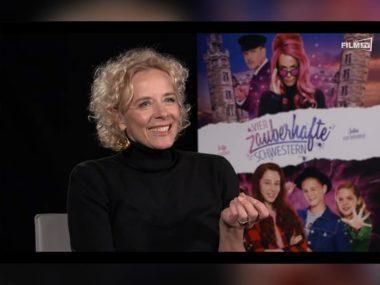 """Katja Riemann vor dem Plakat zum Kinofilm """"Vier zauberhafte Schwester"""""""