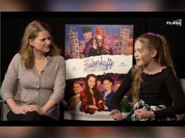 Interviewerin Jessica Neumayer links neben dem Filmplakat zu Vier zauberhafte Schwestern. Rechts danaben Jungstar Lilith Julie Johna