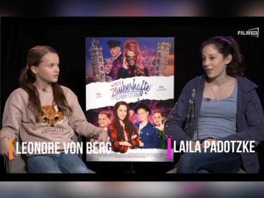Jungstar Leonore von Berg links neben dem Filmplakat zu Vier zauberhafte Schwestern. Rechts neben dem Plakat Laila Padotzke